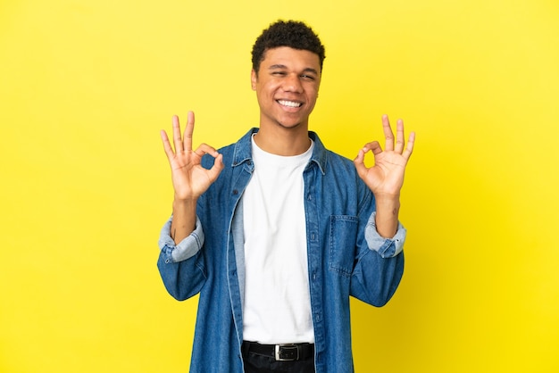 Молодой афроамериканец, изолированные на желтом фоне, показывает знак ок двумя руками