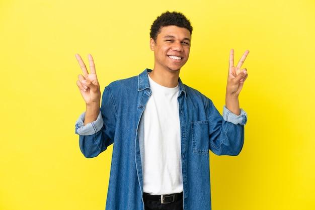 Молодой афроамериканец, изолированные на желтом фоне, показывает знак победы обеими руками