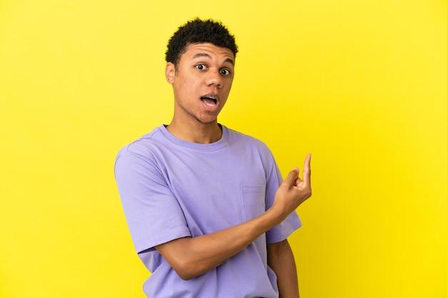 黄色の背景に分離された若いアフリカ系アメリカ人の男は驚いて、側を指しています