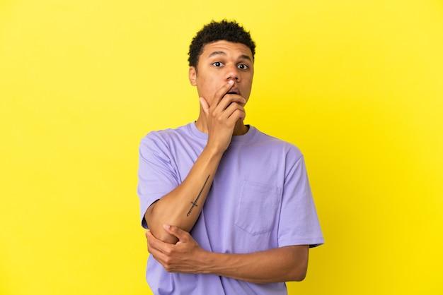 黄色の背景に孤立した若いアフリカ系アメリカ人の男は、右を見ながら驚いてショックを受けました