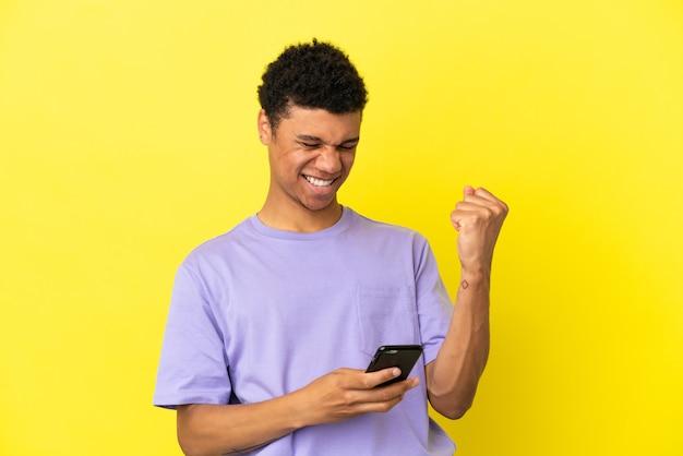 Молодой афроамериканец, изолированные на желтом фоне с телефоном в позиции победы