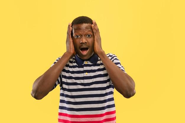 노란색 스튜디오 배경, 인간의 감정 개념에 고립 된 젊은 아프리카 계 미국인 남자.