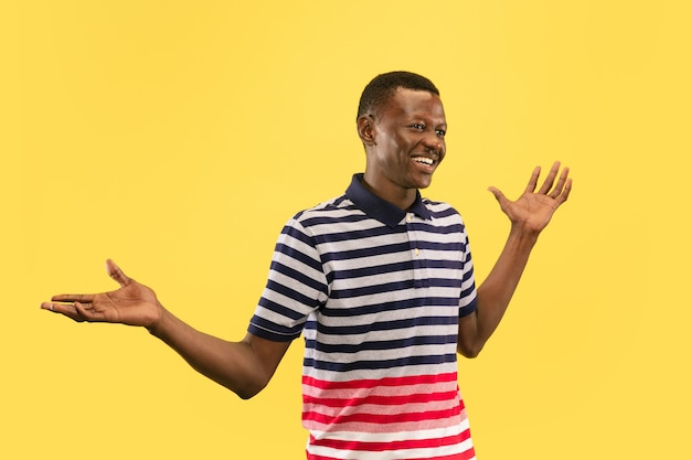 黄色のスタジオの背景、人間の感情の概念に分離された若いアフリカ系アメリカ人の男