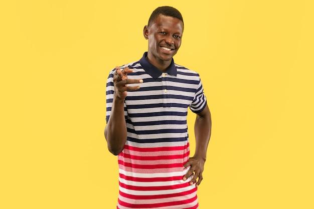 노란색 스튜디오 배경에 고립 된 젊은 아프리카 계 미국인 남자