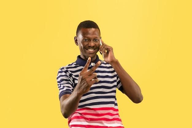 黄色のスタジオの壁、人間の感情の概念に分離された若いアフリカ系アメリカ人の男。