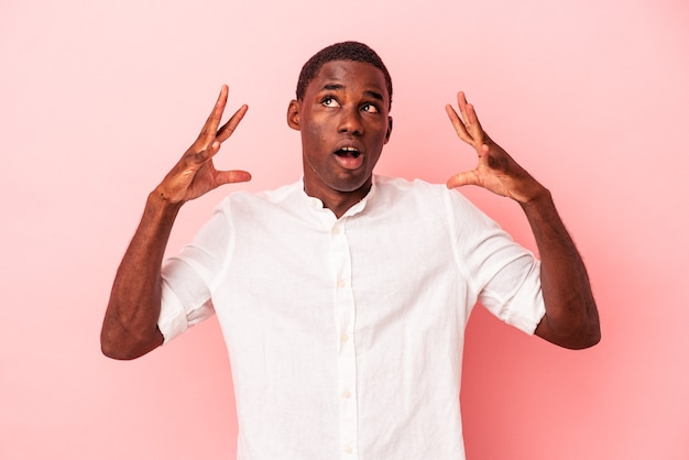 Young african american man isolated on pink background celebrating a victory or success, he is surprised and shocked.