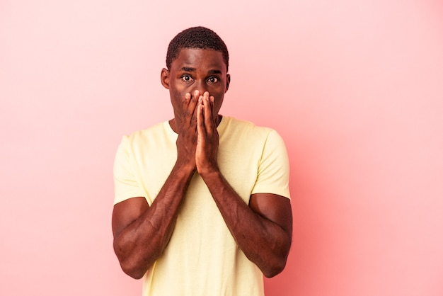 Young african american man isolated on pink background covering mouth with hands looking worried.