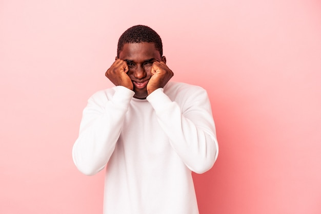 Young african american man isolated on pink background crying, unhappy with something, agony and confusion concept.