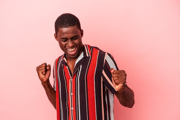 Young african american man isolated on pink background dancing and having fun.