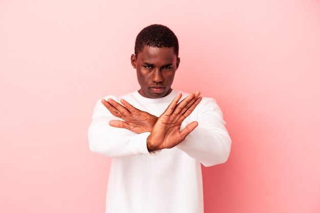 Young african american man isolated on pink background doing a denial gesture