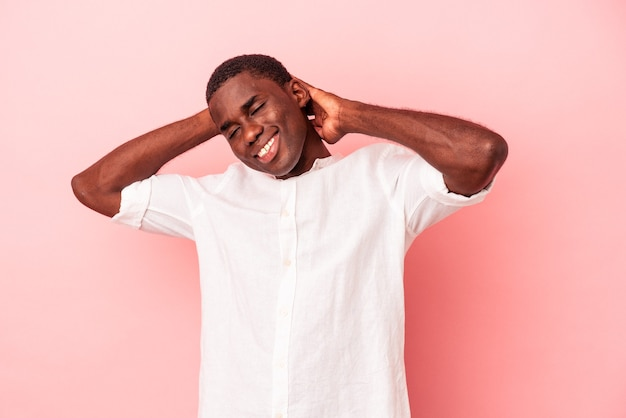 Young african american man isolated on pink background feeling confident, with hands behind the head.