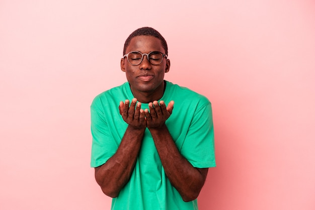 Young african american man isolated on pink background folding lips and holding palms to send air kiss.