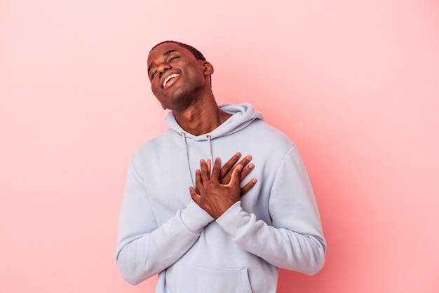 Young african american man isolated on pink background has friendly expression, pressing palm to chest. love concept.