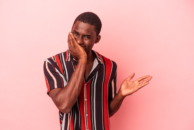 Young african american man isolated on pink background holds copy space on a palm, keep hand over cheek. amazed and delighted.