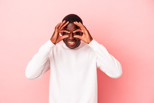 Young african american man isolated on pink background keeping eyes opened to find a success opportunity.