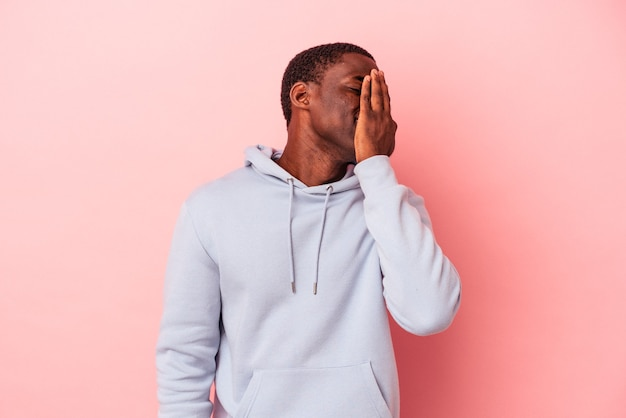 Young african american man isolated on pink background laughing happy, carefree, natural emotion.