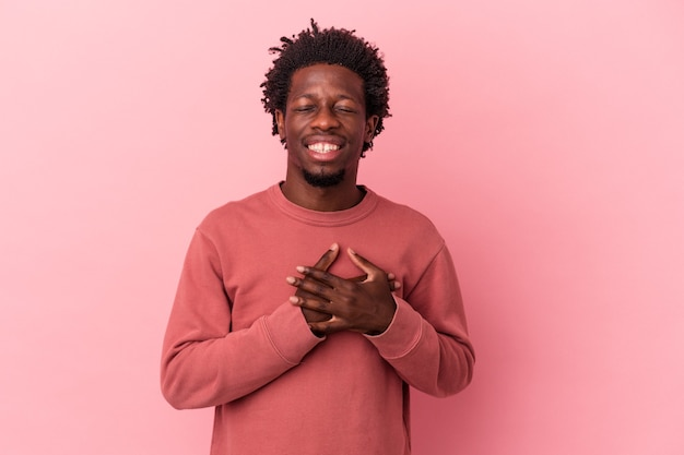 Young african american man isolated on pink background laughing keeping hands on heart, concept of happiness.