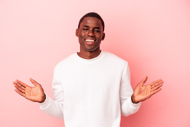 Young african american man isolated on pink background makes scale with arms, feels happy and confident.