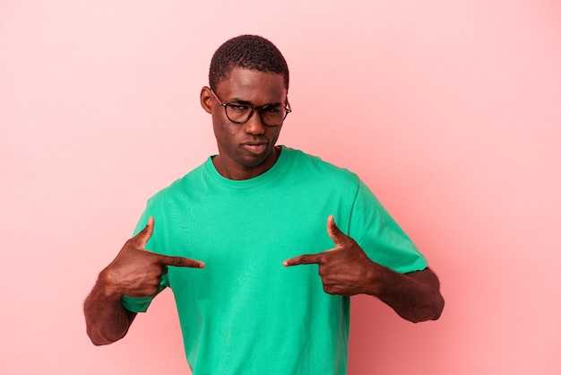 Young african american man isolated on pink background person pointing by hand to a shirt copy space, proud and confident