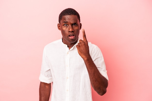 Young african american man isolated on pink background pointing upside with opened mouth.