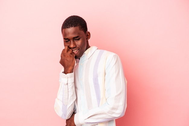 Young african american man isolated on pink background relaxed thinking about something looking at a copy space.