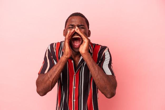 Young african american man isolated on pink background shouting excited to front.