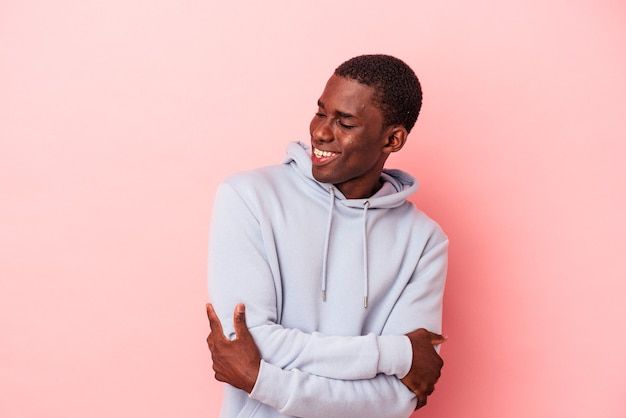 Young african american man isolated on pink background smiling confident with crossed arms.