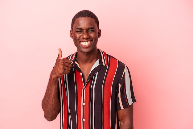 Young african american man isolated on pink background smiling and raising thumb up