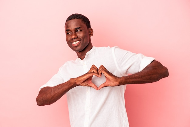 Young african american man isolated on pink background smiling and showing a heart shape with hands.