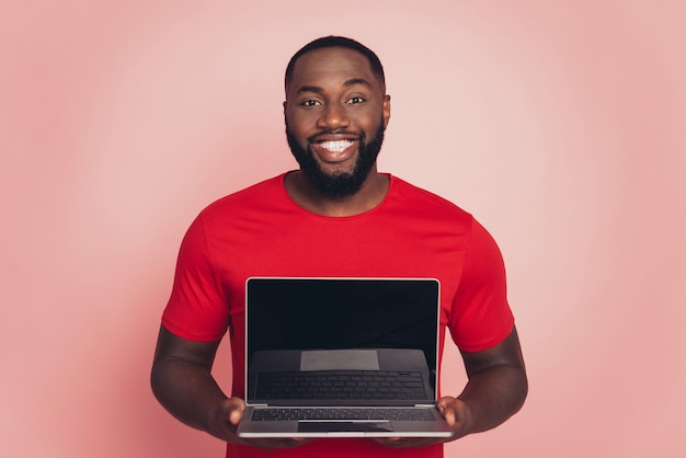 Young african american man isolated on pink background studio hold laptop pc screen