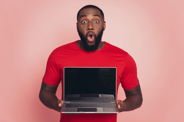 Young african american man isolated on pink background studio hold laptop screen