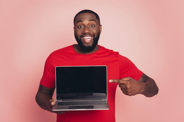 Young african american man isolated on pink background studio hold point index finger laptop pc screen