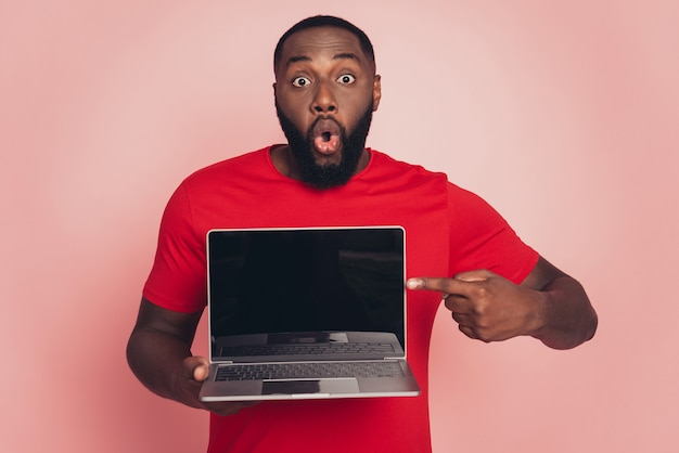 Young african american man isolated on pink background studio hold point index finger laptop screen