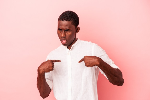 Young african american man isolated on pink background surprised pointing with finger, smiling broadly.