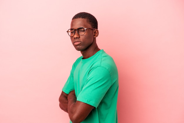 Young african american man isolated on pink background suspicious, uncertain, examining you.