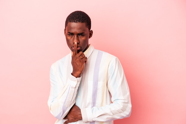 Young african american man isolated on pink background thinking and looking up, being reflective, contemplating, having a fantasy.