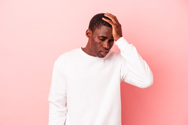 Young african american man isolated on pink background tired and very sleepy keeping hand on head.