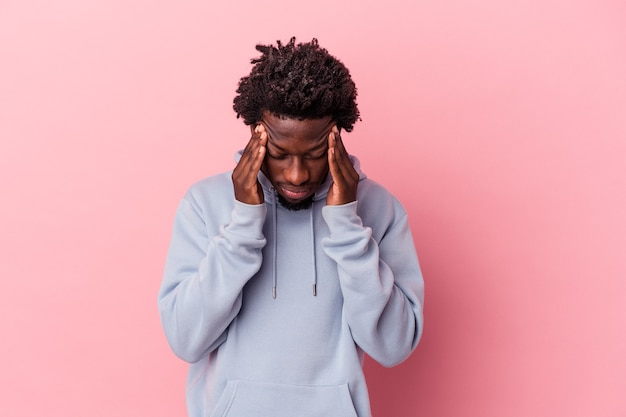 Young african american man isolated on pink background touching temples and having headache.