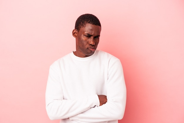 Young african american man isolated on pink background unhappy looking in camera with sarcastic expression.