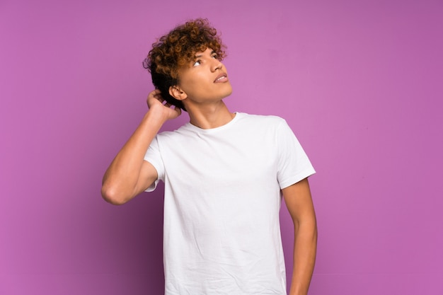Young african american man over isolated purple wall thinking an idea