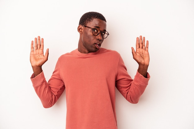 Young african american man isolated on white background being shocked due to an imminent danger