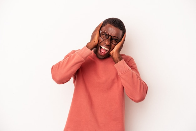 Young african american man isolated on white background covering ears with hands trying not to hear too loud sound.