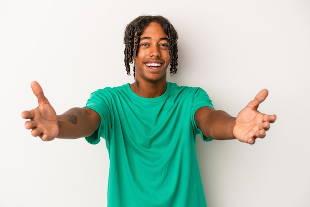 Young african american man isolated on white background feels confident giving a hug to the camera.