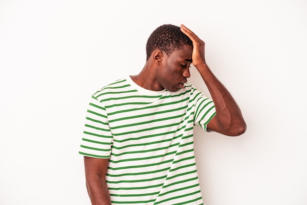 Young african american man isolated on white background forgetting something, slapping forehead with palm and closing eyes.