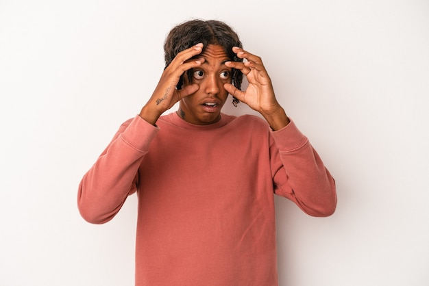 Young african american man isolated on white background keeping eyes opened to find a success opportunity.