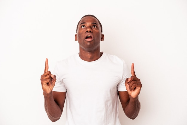 Young african american man isolated on white background pointing upside with opened mouth.