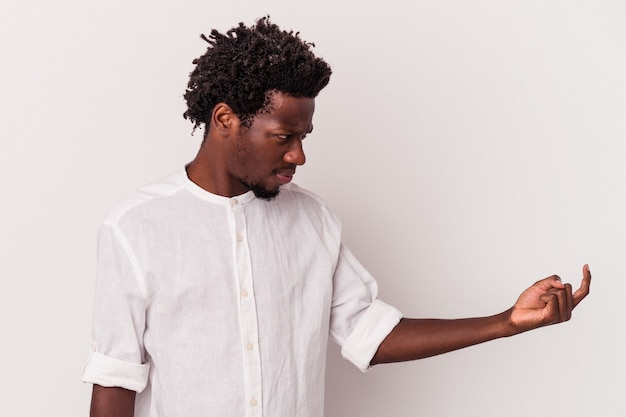 Young african american man isolated on white background  pointing with finger at you as if inviting come closer.