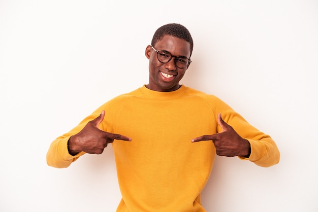 Young african american man isolated on white background points down with fingers, positive feeling.