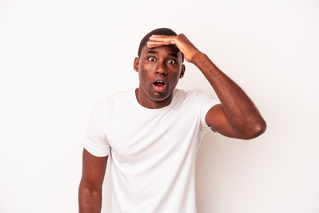 Young african american man isolated on white background shouts loud, keeps eyes opened and hands tense.