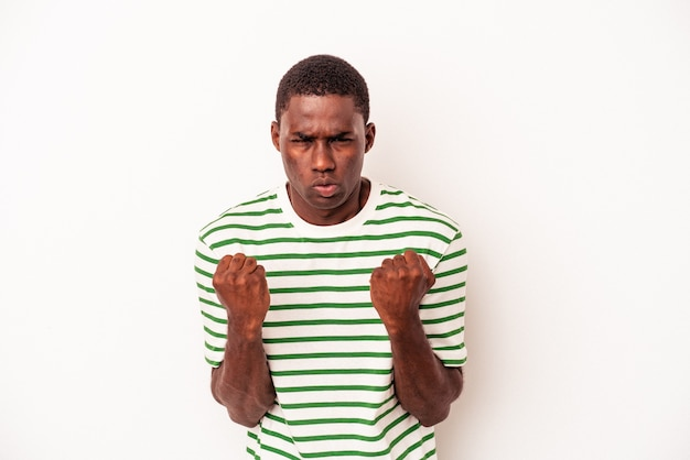 Young african american man isolated on white background showing fist to camera, aggressive facial expression.